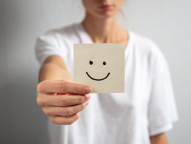 Uma jovem segura um adesivo de papel com um rosto sorridente desenhado na mão estendida. concentre-se na mão e no adesivo, fundo desfocado