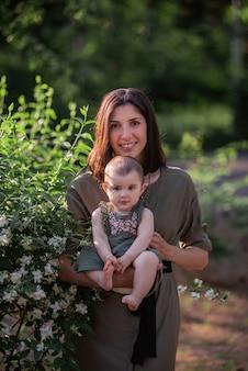 Uma jovem segura um bebê nos braços. uma linda mãe caminha com sua filha em um parque verde perto de arbustos de jasmim