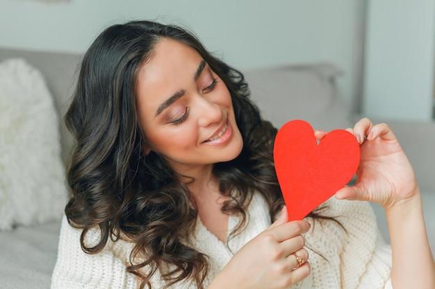 Uma jovem segura um cartão do dia dos namorados em forma de coração. feriados. dia dos namorados.