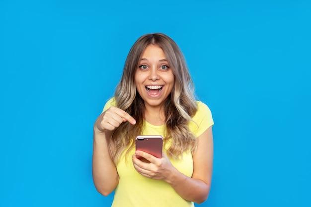 Uma jovem segura um celular na mão e aponta para a tela com o dedo