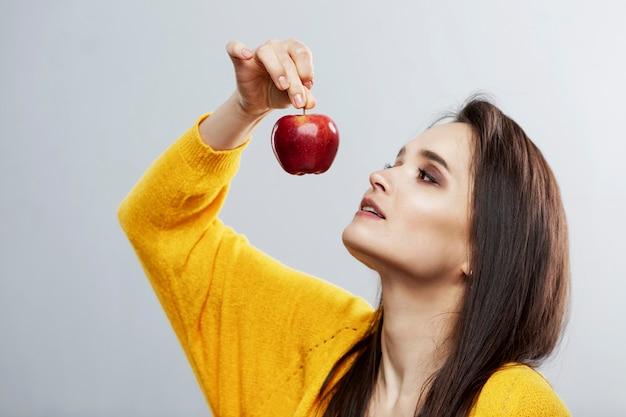 Uma jovem segura uma maçã vermelha nas mãos. saúde e vitaminas. plano de fundo cinza.