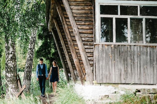 Uma jovem segurando a mão do marido caminhando ao lado de uma bétula perto de uma velha casa de madeira