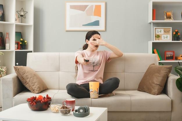 Uma jovem segurando o controle remoto da tv e sentada no sofá atrás da mesa de centro da sala de estar com um olho coberto de medo
