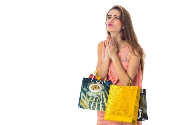 Uma jovem segurando pacotes com lojas e pensando em close-up