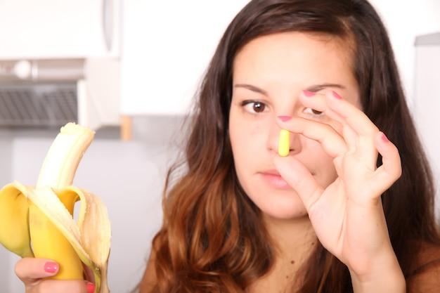 Uma jovem segurando um comprimido de suplemento em uma mão e uma banana na outra.