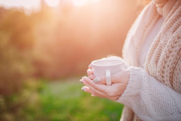 Uma jovem segurando um copo de bebida quente e sorrindo para a floresta de outono