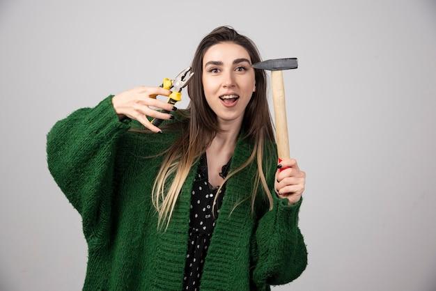 Uma jovem segurando um martelo e um alicate nas mãos.