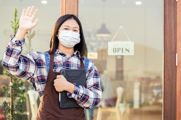 Uma jovem segurando um tablet com diga oi e tem uma placa que diz bem-vindo, estamos abertos no café