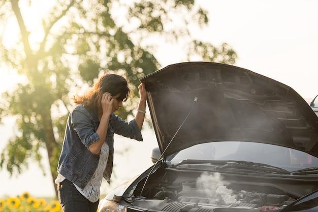 Uma jovem senhora com um carro preto que quebrou na estrada. quer ajuda com o carro quebrado.