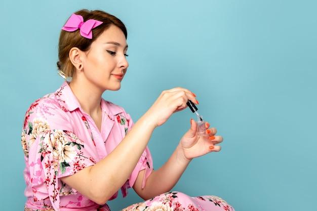 Uma jovem senhora em uma flor com um vestido rosa pintando as unhas em azul