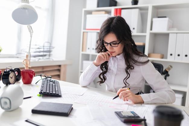 Uma jovem senta-se à mesa do escritório, detém uma caneta na mão e olha para os documentos.