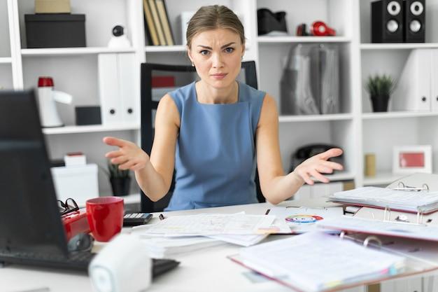 Uma jovem senta-se à mesa do escritório e estende os braços para os lados.