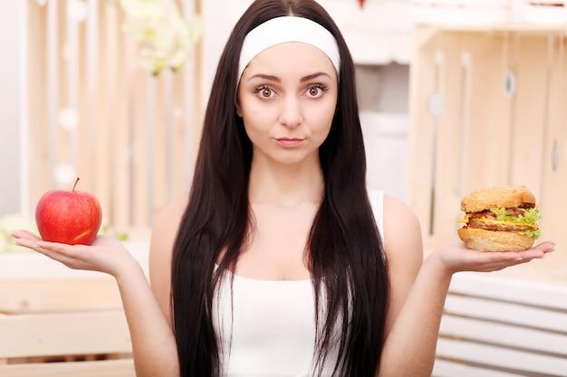 Uma jovem senta-se em casa e faz uma escolha entre comida saudável e hambúrguer