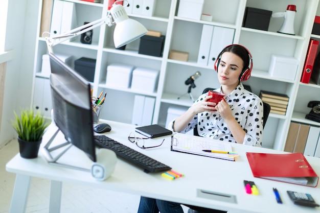 Uma jovem senta-se em fones de ouvido em uma mesa no escritório, detém um copo vermelho nas mãos e olha para o monitor.