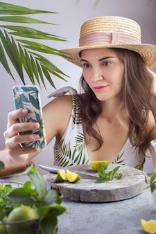 Uma jovem senta-se em uma mesa com um chapéu e leva um selfie