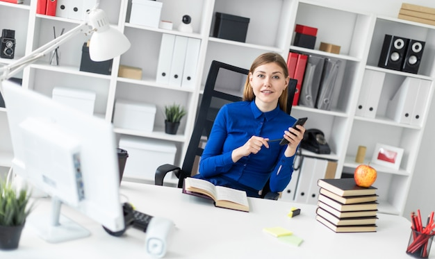 Uma jovem senta-se em uma mesa de computador e possui um telefone na mão. antes da menina encontra-se um livro aberto.