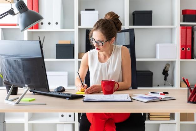 Uma jovem senta-se em uma mesa em seu escritório, detém um lápis nas mãos e grava-los em um adesivo