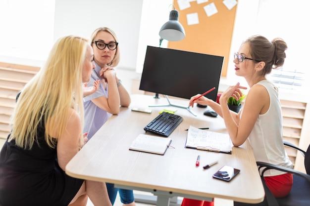 Uma jovem senta-se em uma mesa em seu escritório e fala com dois copartners