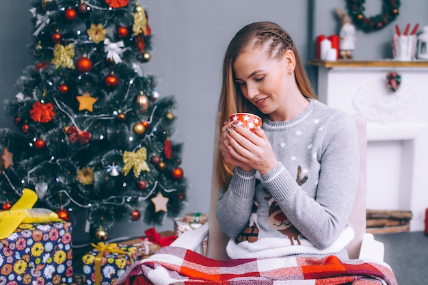 Uma jovem senta-se embrulhada em um cobertor xadrez com uma xícara de café quente junto à lareira, perto da árvore do ano novo.