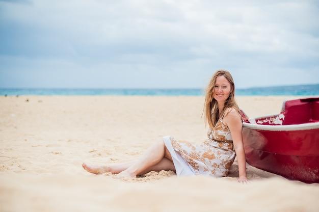 Uma jovem senta-se na praia, encostado a um barco
