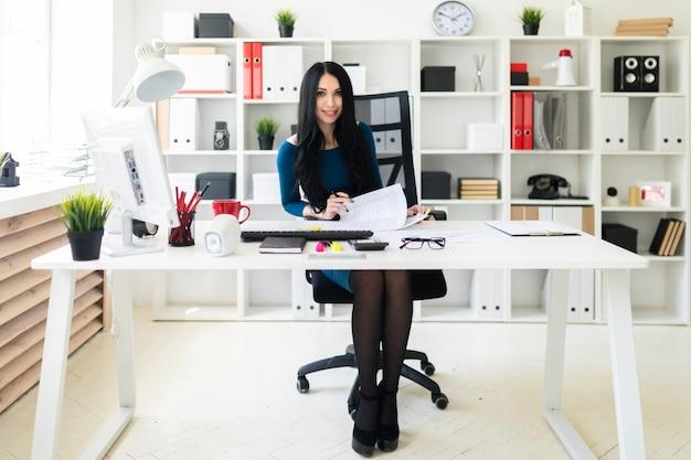 Uma jovem senta-se no escritório à mesa, detém uma caneta na mão e preenche os documentos