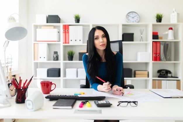 Uma jovem senta-se no escritório à mesa, segura uma caneta na mão e preenche os documentos.