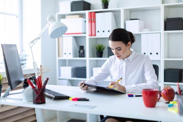 Uma jovem senta-se no escritório, detém uma caneta na mão e olha através de documentos.