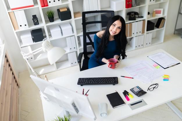 Uma jovem senta-se no escritório na mesa e detém um copo vermelho nas mãos dela