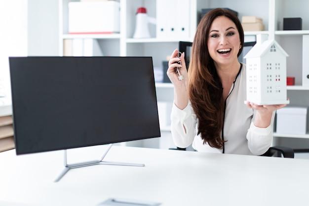 Uma jovem sentada à mesa, segurando as chaves e o layout da casa. em cima da mesa é um monitor.