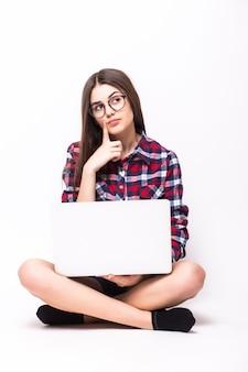 Uma jovem sentada no chão com um laptop branco