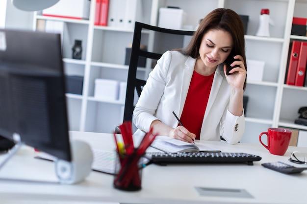 Uma jovem sentada no escritório, na mesa do computador e falando ao telefone.