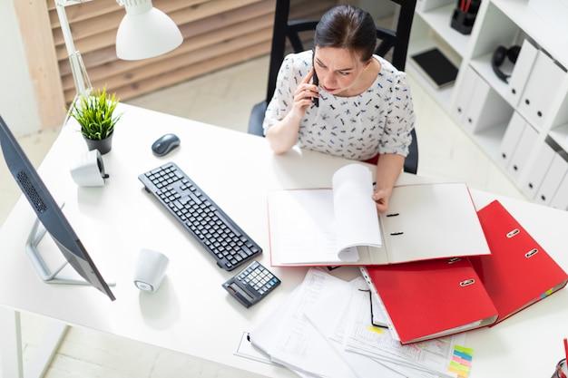 Uma jovem sentada no escritório, na mesa do computador, trabalhando com documentos e falando ao telefone.