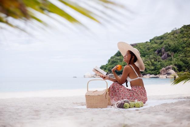 Uma jovem sentada no tapete da praia com um chapéu de palha e uma roupa de malha branca