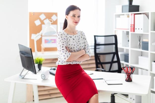 Uma jovem sentou-se em uma mesa no escritório.