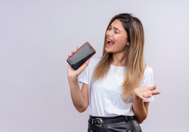 Uma jovem séria em uma camiseta branca cantando uma música segurando o celular como um microfone em uma parede branca