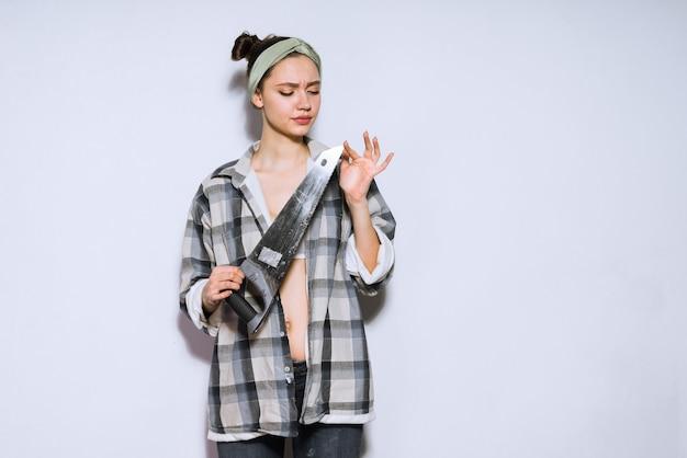 Uma jovem séria segurando uma serra de metal afiada nas mãos, fazendo reparos no apartamento