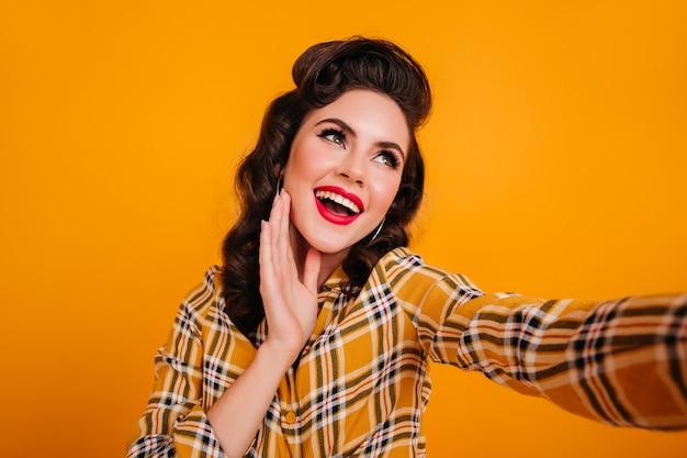 Uma jovem sonhadora com lábios vermelhos, tomando uma selfie. foto de estúdio da senhora pin-up em camisa quadriculada, posando em fundo amarelo.