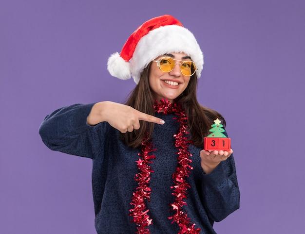 Uma jovem sorridente caucasiana de óculos de sol com chapéu de papai noel e guirlanda no pescoço segura e aponta para o enfeite de árvore de natal isolado na parede roxa com espaço de cópia