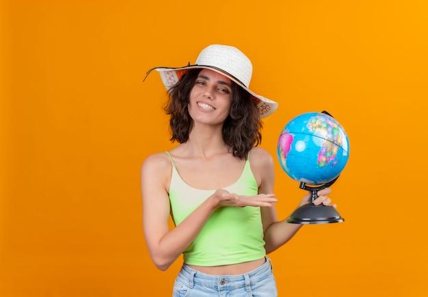 Uma jovem sorridente, com cabelo curto em um top verde e chapéu de sol mostrando um globo