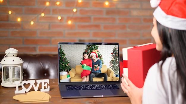 Uma jovem sorridente com chapéu de papai noel vermelho fazendo videochamada na rede social com família e amigos no dia de natal.