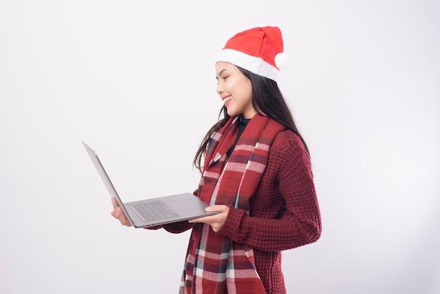 Uma jovem sorridente com chapéu de papai noel vermelho fazendo videochamada na rede social