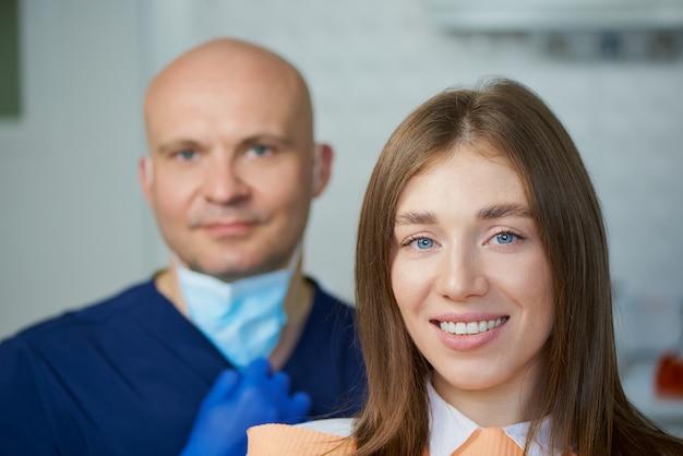Uma jovem sorridente com seu dentista de meia-idade careca no consultório de um dentista