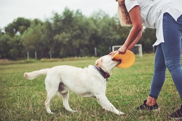Uma jovem sorridente com uma expressão feliz e feliz brinca com seu amado cachorro.
