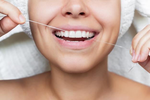 Uma jovem sorridente com uma toalha branca na cabeça depois do banho passando fio dental nos dentes