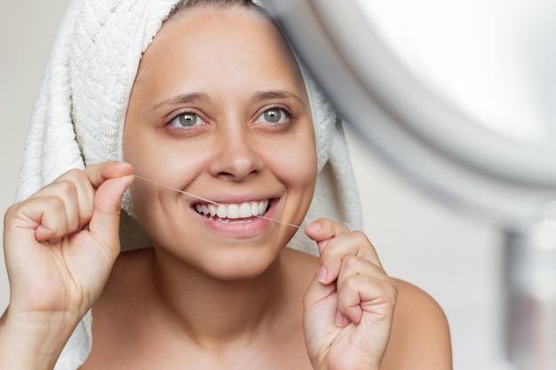 Uma jovem sorridente com uma toalha branca na cabeça, passando fio dental nos dentes, olhando no espelho
