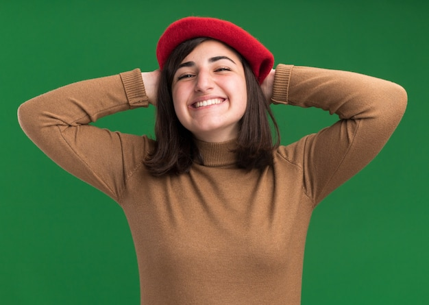 Uma jovem sorridente e bonita caucasiana com chapéu boina coloca as mãos na cabeça atrás, isolada em uma parede verde com espaço de cópia