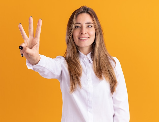 Uma jovem sorridente e bonita caucasiana gesticula três com os dedos na laranja