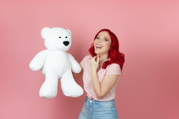 Uma jovem sorridente e encantada de cabelo vermelho segura um grande ursinho de pelúcia branco