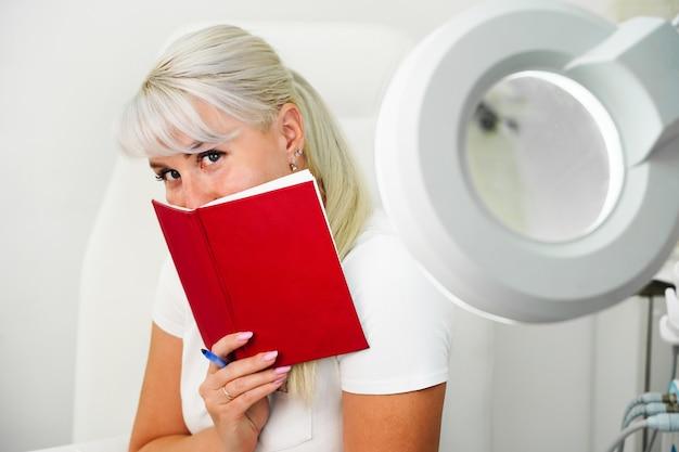 Uma jovem sorridente e envergonhada com um caderno vermelho nas mãos está sentada no escritório da esteticista ...