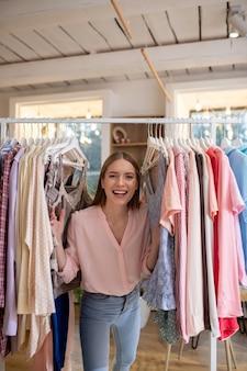 Uma jovem sorridente em pé entre as roupas criadas por ela
